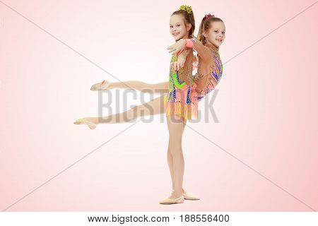 Two adorable little twin girls, gymnastics in the sports school. Girls beautiful gymnastic leotards. They do the splits.Pale pink gradient background.