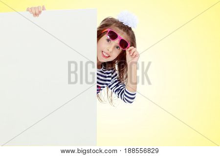 The little blonde girl with long hair and with a white bow on her head , in a blue striped summer dress.The girl in the dark sunglasses peeking from behind the banner.On a yellow gradient background.