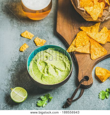 Mexican corn chips, fresh guacamole sauce and glass of beer on wooden serving board over grey concrete table background, selective focus, square crop