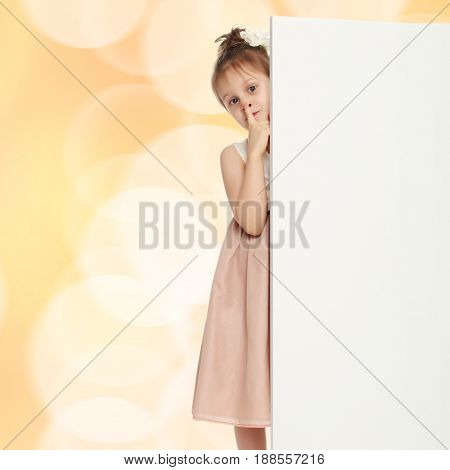 Cute little girl peeking out from behind the white banner.She keeps the index finger in the lips, a gesture of quiet.Brown festive, Christmas background with white snowflakes, circles.