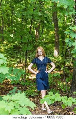 Beautiful woman in elegant dress and charming smile posing in the park. Business girl walks after work.