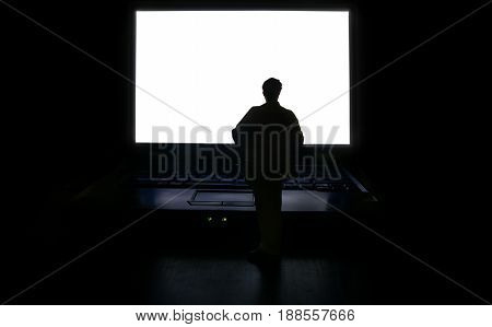 Miniature human figure standing in front of a white computer screen