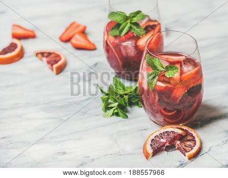 Blood orange and strawberry summer Sangria. Fruit refreshing rose wine cocktails in glasses with ice cubes and fresh mint leaves over marble table background, selective focus, copy space