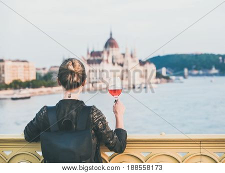 Young woman tourist standing with glass of rose wine at Margaret bridge in Budapest, Hungarian Parliament building and Duna river at background