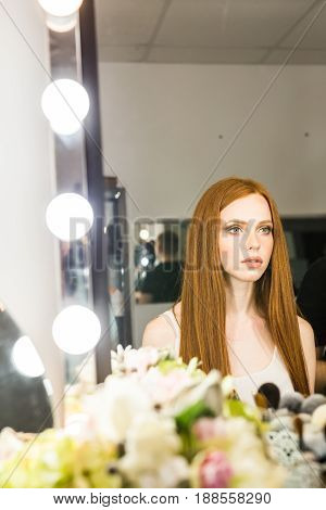 beautiful red-haired woman sitting in front of a mirror.
