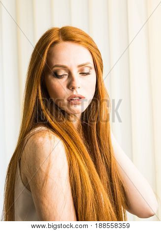 Beautiful model girl with shiny red straight long hair . Care and hair products