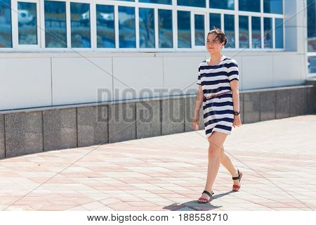 Street fashion concept. Young beautiful woman in the city. Beautiful girl wearing striped dress walking on the street