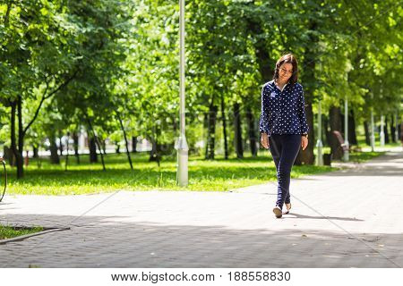 Beautiful young woman walking in summer park