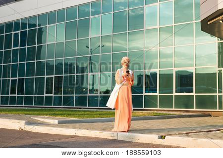 happy islamic woman using smart phone outdoors