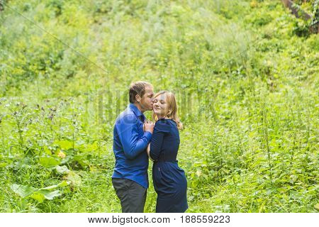Young loving couple hugging outdoors on the green grass.