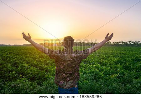 Farmer man standing with arms raised on the green field before the harvest. People freedom on nature concept.