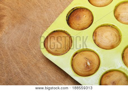 Sweet muffins on wooden background baked in silicone form. There is space for text placement
