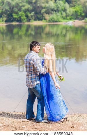Young happy couple having fun beside river in summer sunny day