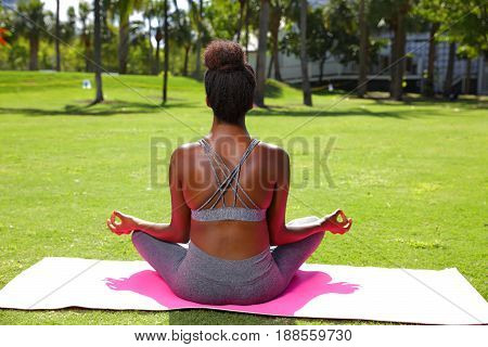Image of a black female fitness model posing in the park