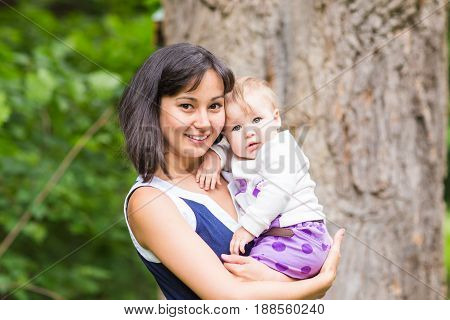 Mixed race happy mother with baby girl outdoors portrait.