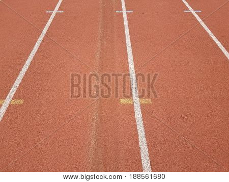 orange running track lanes with car tire marks