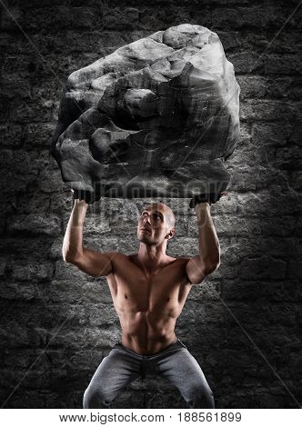 Muscular man with determination lifts a big boulder