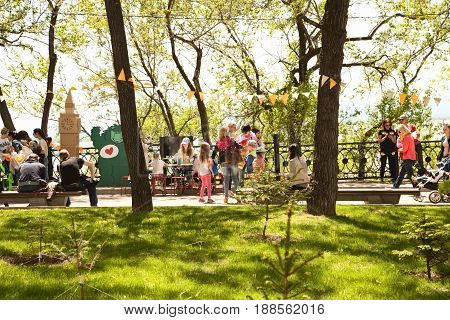 Khabarovsk Russia - May 20 2017: Happy people walking on a festive tranquil street in summer light. Families having fun on a holiday at green decorated park