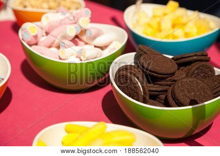 Chocolate cookies marshmallows and other confectionery in bright bowls. Fun colorful close-up of various types of sweets. Tasty snacks at birthday buffet