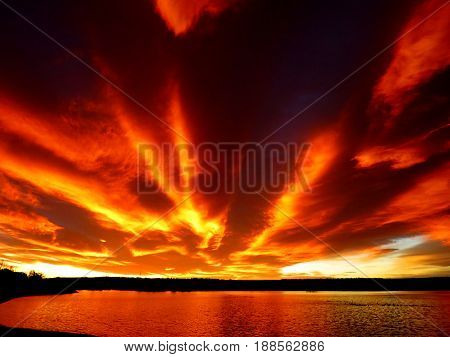 brilliant orange streaking cloud sunrise over a calm lake