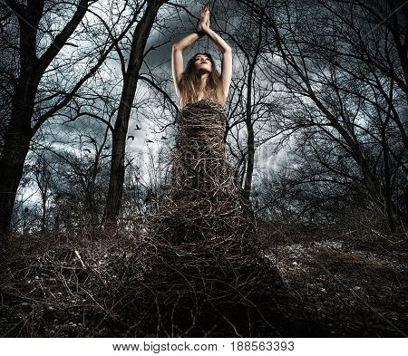 Woman dressed in branches in the woods. connection between nature and human concept