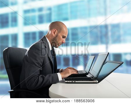 Tired businessman works with three laptop in the office
