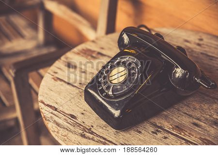 Old Telephone Black Color On Wood Table. Classic Retro Vintage Style Rotary Dial Calling Telephone T