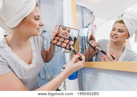 Woman In Bathroom Applying Contour Bronzer On Brush