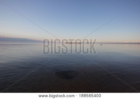 A calm day on Lake Michigan.  A rock an be seen submerged underwater