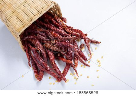 Closeup of red dry chili peppers in basket on white background.