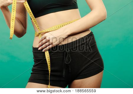 Weight loss slim body healthy lifestyle concept. Fit fitness girl measuring her waistline with measure tape on green