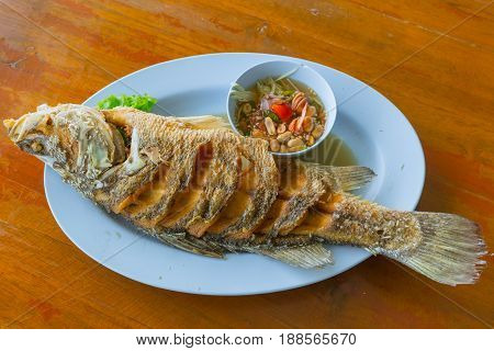 Thai Sea Food Fish Deep Fried With Spicy Dip Suace Served On Wood Table.