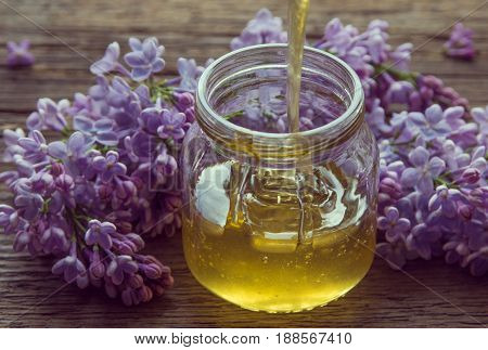 Organic Honey Pours In A Glass Jar, Wrapped In A Spring Flower, Purple Lilac