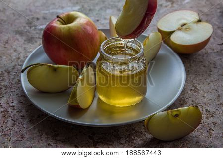 Organic Honey In Glass Jar And Red Apple On The Plate