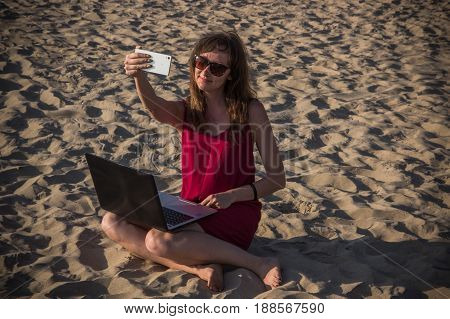 Young Woman In Red Dress With Computer And Smartphone On The Beach. Freelance And Downshifting Conce