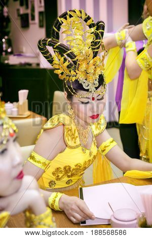asian actress in a yellow traditional chinese stage costume reading menu at the restaurant