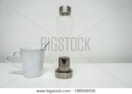 isolated white ceramic cup and handy glass bottle for water