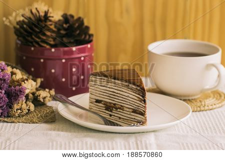 Homemade chocolate crepe cake or mille crepe cake  topping with dark chocolate sauce, Chocolate cake on white plate. Crepe cake chocolate sauce so delicious bitter and sweet. Homemade chocolate cake on rustic wood table serve with tea or coffee. Enjoy on