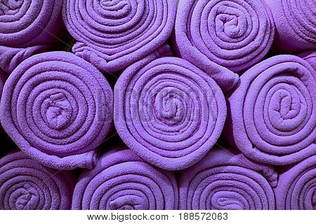 Heap of Rolled up Bright Purple Colored Fleece Blankets, for Background, Fabric Texture