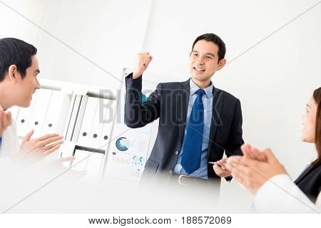 Powerful businessman as a meeting leader clenching his fist empowering his colleagues in front of the room