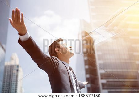 Success businessman in the city raising his arms open palms with face looking up - financial freedom concepts double exposure effect