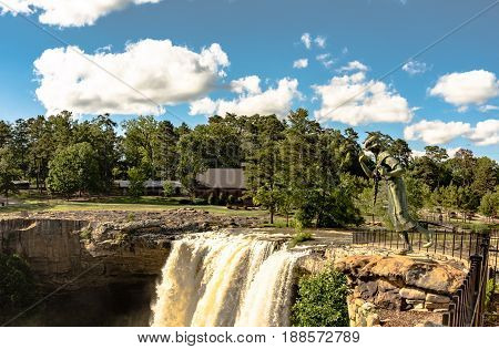 Gadsden Alabama USA - May 25 2017: Noccalula Falls including the nine-foot-tall bronze statue of Noccalula a young Cherokee woman who plunged to her death after being ordered by her father to marry a man she did not love. The falls and park are named afte