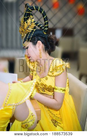 asian actress in a yellow traditional chinese stage costume reading menu at the restaurant profile view