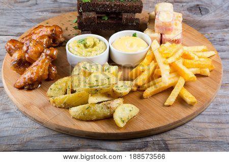 Diferent beer snacks served on a round board