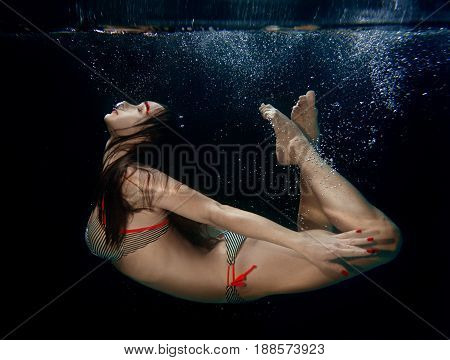 Underwater portrait of young attractive beautiful woman (free diver) in yoga asana on the dark background