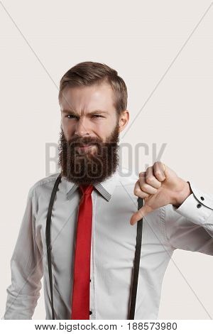 Manager do not like salary. Portrait of creative bearded hipster show finger down. Unlike and dislike concept. Cropped shot of unhappy businessman. Frowning face of 30 years person.