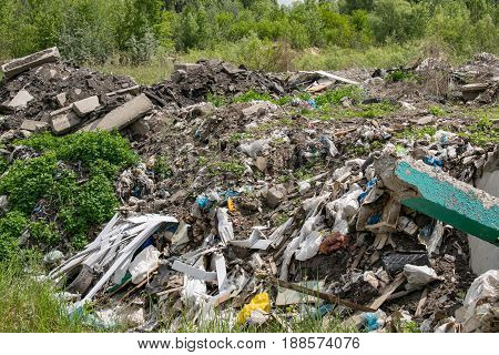 Illegal garbage dumping outside near the forest in summer