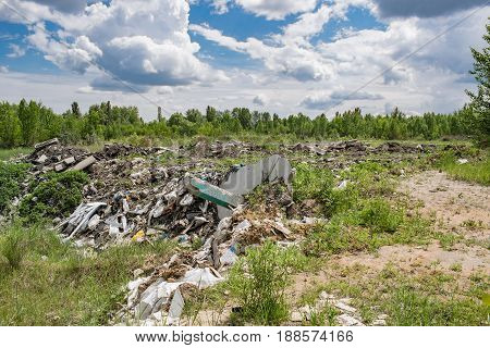 Illegal garbage dumping outside the forest in summer
