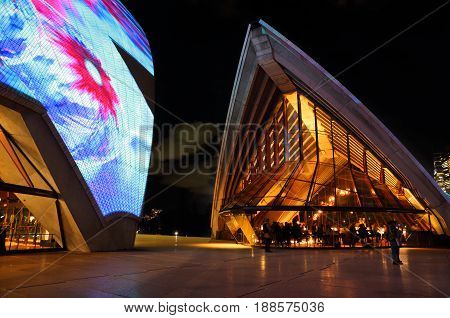 SYDNEY AUSTRALIA - MAY 26 2017; Tourists and locals around the Opera House and restaurant which is illuminated with various moving designs during the Vivid Sydney annual public event.