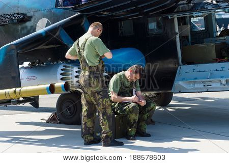 BERLIN GERMANY - MAY 21 2014: Technicians inspect attack helicopter with transport capabilities Mil Mi-24 Hind. Czech Air Force. Exhibition ILA Berlin Air Show 2014